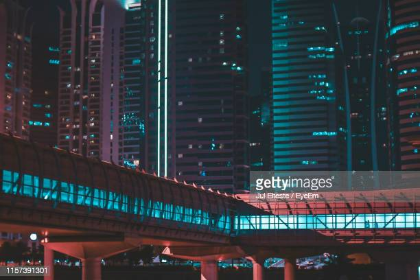 illuminated elevated walkway and modern buildings at night - elevated walkway stock pictures, royalty-free photos & images