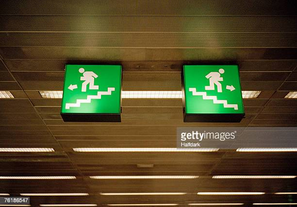 Illuminated emergency exit signs on a ceiling