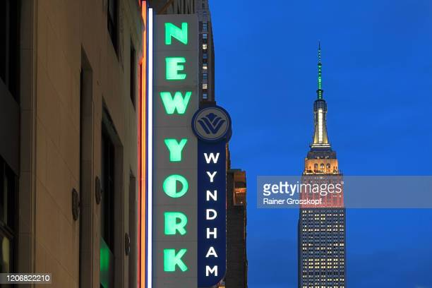 "illuminated empire state building at dusk with a ""new yorker"" neon sign - rainer grosskopf stock pictures, royalty-free photos & images"