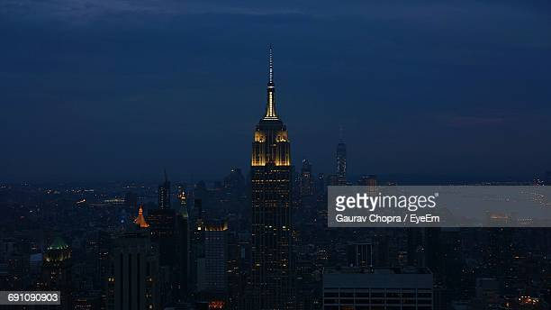 Illuminated Empire State Building By Cityscape Against Sky At Night