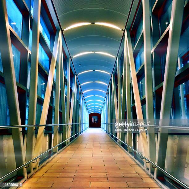 illuminated empty elevated walkway at night - arch architectural feature stock pictures, royalty-free photos & images