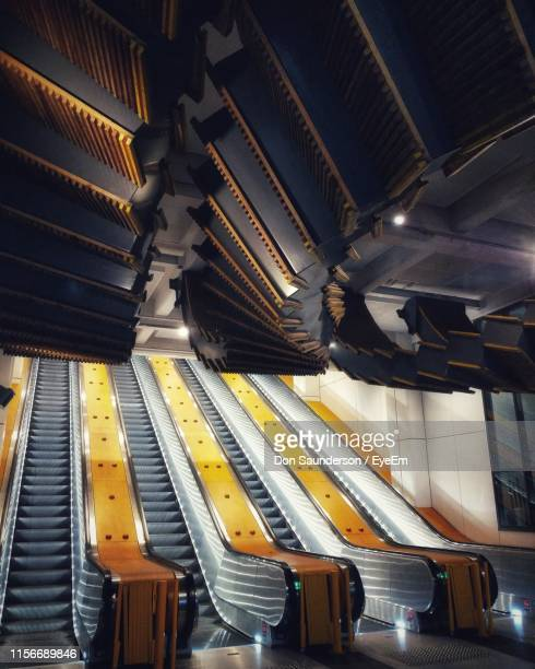 illuminated empty escalators in built structure - railings stock pictures, royalty-free photos & images