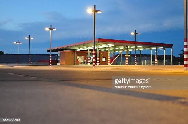 illuminated empty parking lot against sky at dusk - erlangen stock photos and pictures