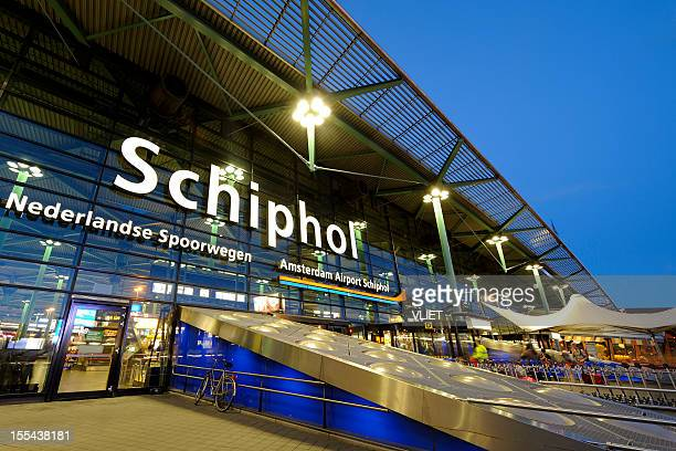 illuminated entrance of amsterdam airport schiphol at night - schiphol airport stock photos and pictures