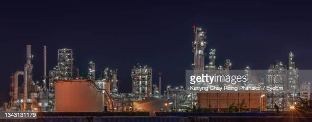 illuminated factory against sky at night - greenpeace stock pictures, royalty-free photos & images