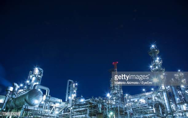 illuminated factory against sky at night - oil refinery stock pictures, royalty-free photos & images