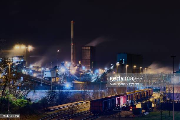 illuminated factory against sky at night - ruhr stock pictures, royalty-free photos & images