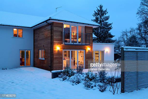 illuminated family home in snow - winter house stock pictures, royalty-free photos & images