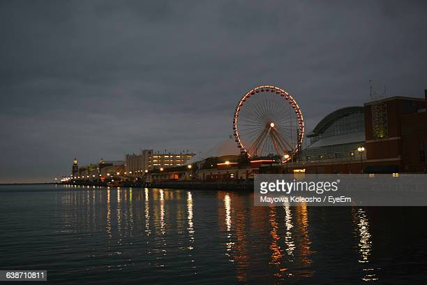 illuminated ferris wheel at navy pier in sea against sky - navy pier stock pictures, royalty-free photos & images