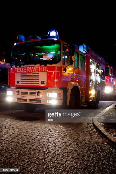 Beleuchtet Feuerwehrmann Fahrzeuge im Haus Feuer