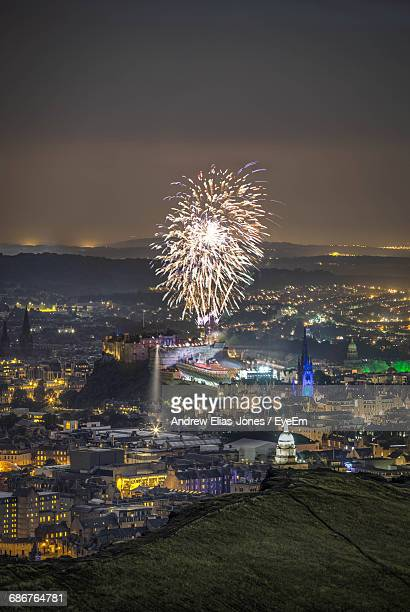 Illuminated Fireworks Over Cityscape Against Sky At Night