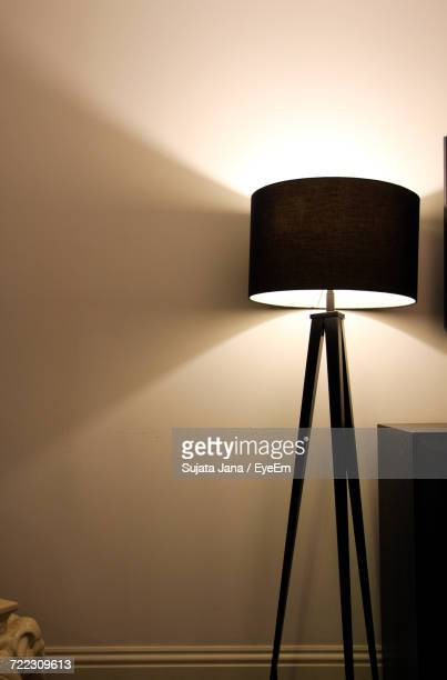 Illuminated Floor Lamp Against Wall At Home