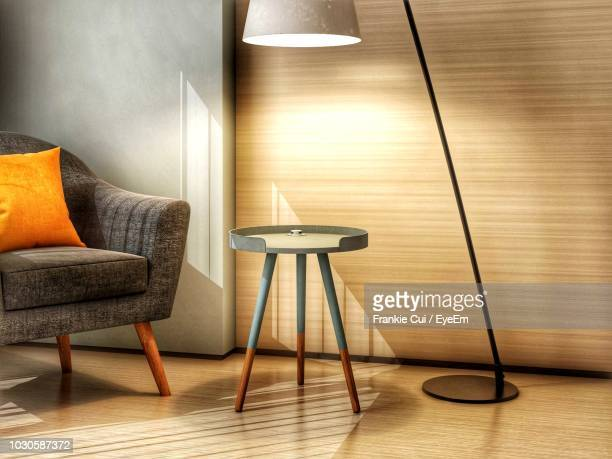 illuminated floor lamp by table in modern home - 現代的 ストックフォトと画像