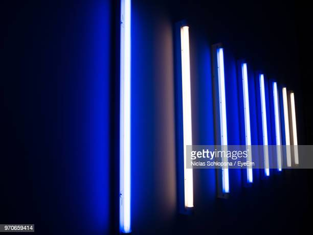 illuminated fluorescent lights on wall in darkroom - fluorescent light stock pictures, royalty-free photos & images