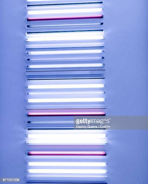 illuminated fluorescent lights on wall - fluorescent light stock pictures, royalty-free photos & images