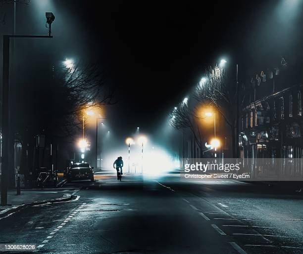 illuminated foggy city street at night - midnight stock pictures, royalty-free photos & images