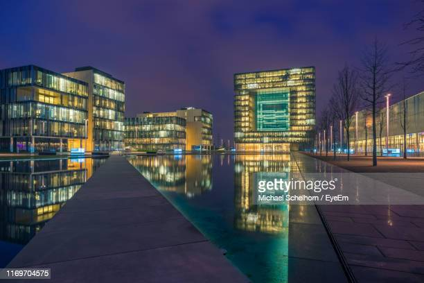 illuminated footpath amidst buildings against sky at night - ruhr stock pictures, royalty-free photos & images