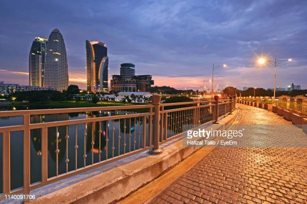 illuminated footpath in city against sky at dusk - putrajaya stock photos and pictures