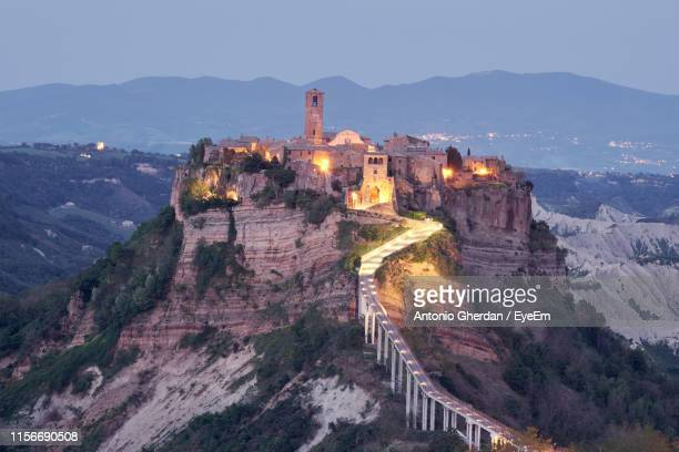 illuminated fort on mountain against sky at dusk - civita di bagnoregio foto e immagini stock