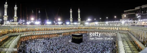 illuminated fountain by building against sky at night - hajj stock pictures, royalty-free photos & images