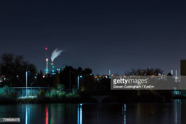 illuminated fountain by river against sky in city at night - steven cottingham stock-fotos und bilder