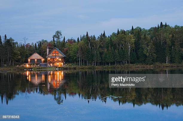 Illuminated garage and handcrafted spruce log home on edge of lake at dusk, Quebec, Canada