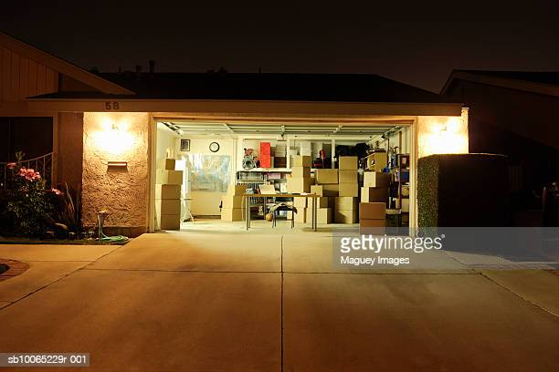 illuminated garage with open door - garage stock pictures, royalty-free photos & images