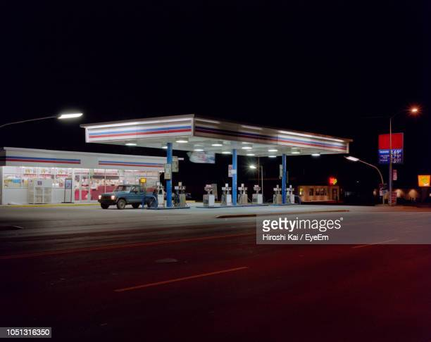 illuminated gas station at night - gas station stock pictures, royalty-free photos & images