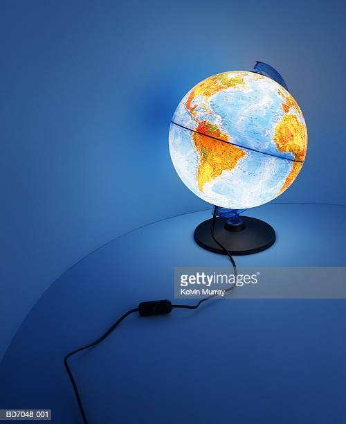 illuminated globe on curved background - mappamondo foto e immagini stock