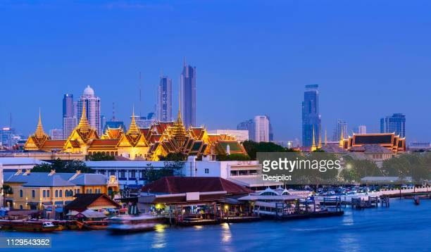Illuminated Grand Palace with the Modern Bangkok City Skyline in the Background at Sunset, Thailand.
