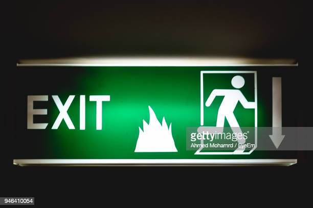 Illuminated Green Exit Sign Against Black Background