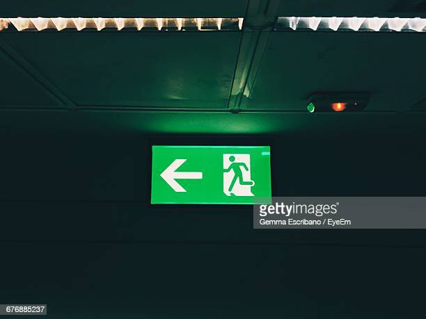 illuminated green exit sign in building - exit sign stock pictures, royalty-free photos & images