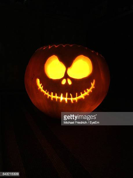 illuminated halloween pumpkin against black background - halloween lantern stock photos and pictures