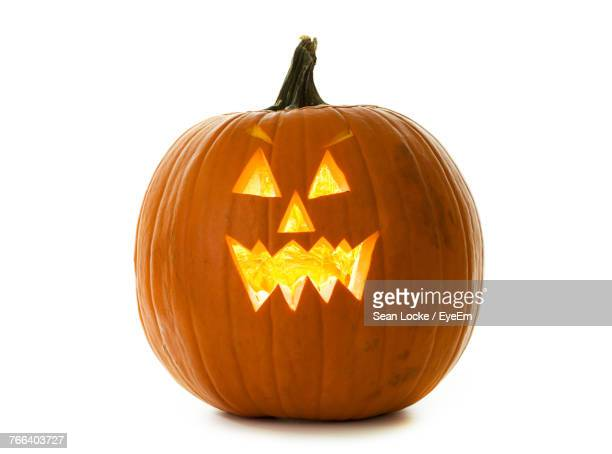 illuminated halloween pumpkin against white background - jack o' lantern stock photos and pictures