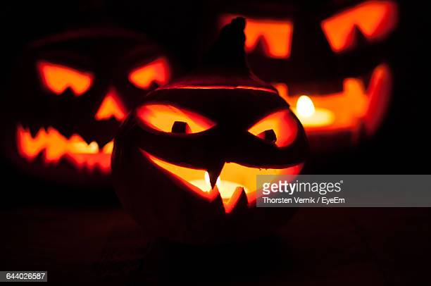 illuminated halloween pumpkins against black background - scary pumpkin faces stock photos and pictures