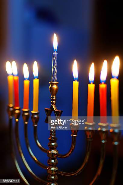 illuminated hanukkah candles on gold menorah with star of david decoration, blue background - hanukkah imagens e fotografias de stock