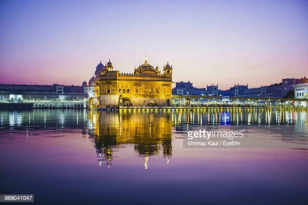 Illuminated Harmandir Sahib Against Clear Sky During Sunset
