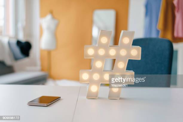 Illuminated hashtag sign on table in fashion studio
