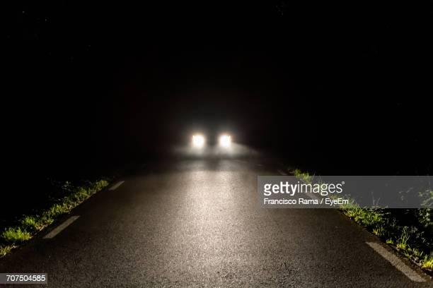 illuminated headlights of vehicle on road at night - headlight stock pictures, royalty-free photos & images