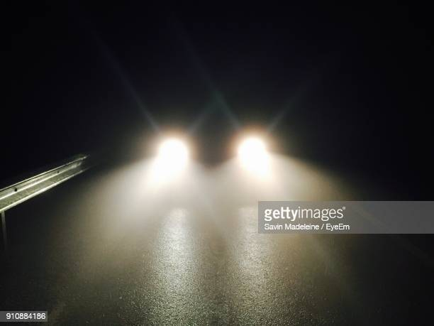Illuminated Headlights On Street At Night