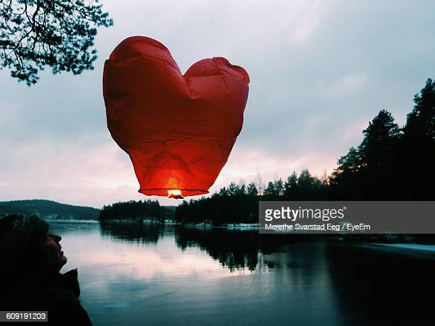 Illuminated Heart Shape Paper Lantern Over Lake Against Cloudy Sky