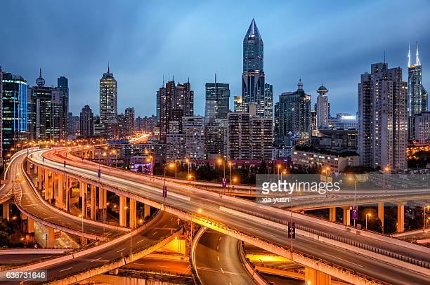 Illuminated highway interchange against city skyline,Shanghai