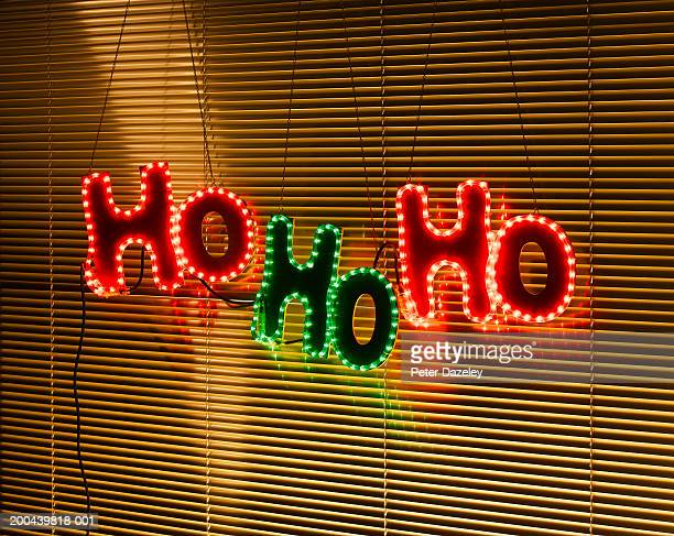 Illuminated 'Ho Ho Ho' decoration behind blind on window