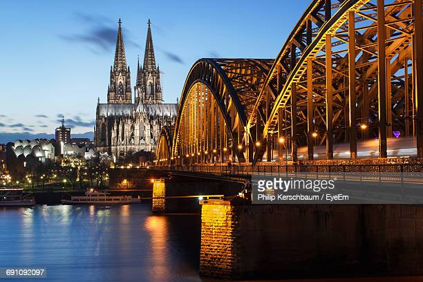illuminated hohenzollern bridge over river rhine by cologne cathedral at dusk - cologne stock pictures, royalty-free photos & images