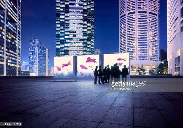illuminated hong kong skyline with people looking at flower images - arts culture et spectacles photos et images de collection