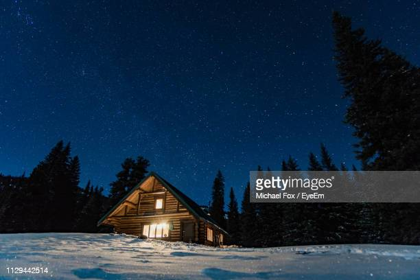 illuminated house on snowcapped landscape against star field sky - tranquil scene stock pictures, royalty-free photos & images