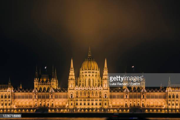 illuminated hungarian parliament  against sky at night - lutai razvan stock pictures, royalty-free photos & images