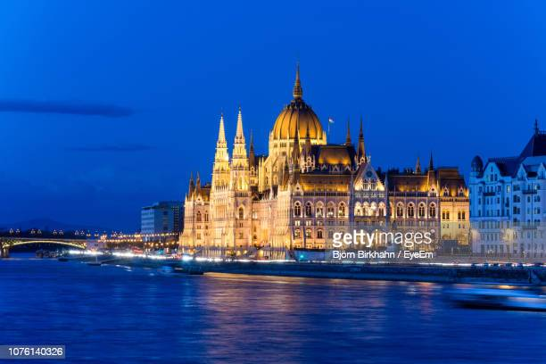illuminated hungarian parliament building by danube river against blue sky - eastern european stock pictures, royalty-free photos & images