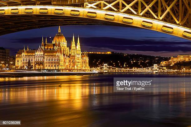 Illuminated Hungarian Parliament Building By Danube River