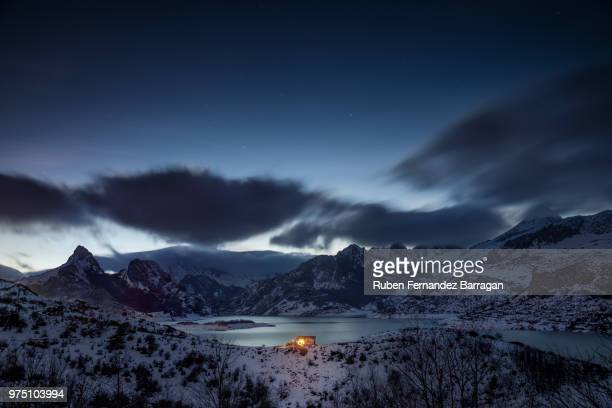 illuminated hut by reservoir with mountains in background, riano, leon, spain - レオン県 ストックフォトと画像